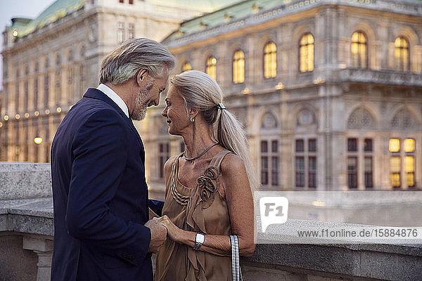 Ein Paar  das sich gegenübersteht und eng an den Händen hält  mit einem Wiener Gebäude im Hintergrund.
