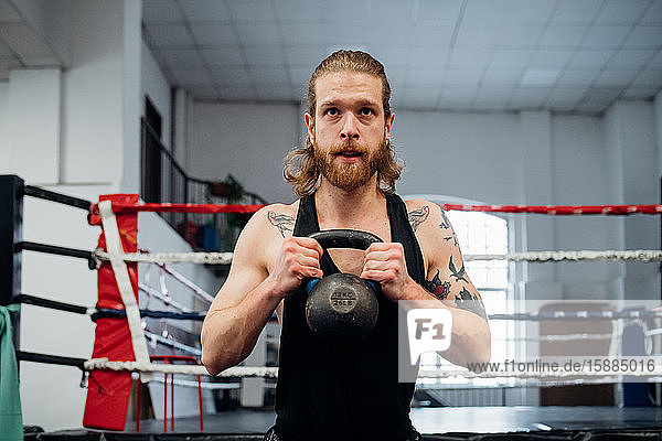 Mann steht mit einer Kesselglocke in Brusthöhe vor einem Boxring.