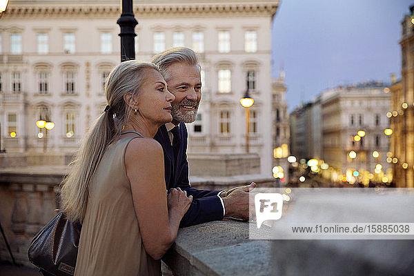 Ein Paar  das sich am Abend an eine Balustrade mit Blick auf Wien lehnte.