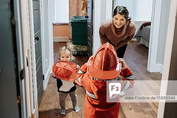 Eine Mutter lächelt ihr Kind an  das als Feuerwehrmann verkleidet ist.