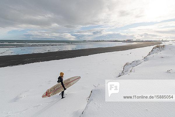 Rückansicht einer Frau  die einen Neoprenanzug trägt und ein Surfbrett in der Hand hält  beim Spaziergang an einem verschneiten Strand.