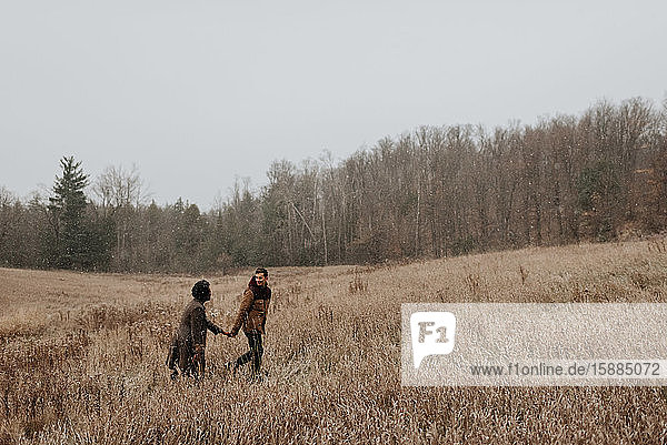 A couple holding hands and looking at each other walking through long grasses in a wintry landscape.