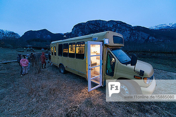 Campervan in a rocky landscape at dusk with the light on inside and the door open  group of people standing towards the rear.