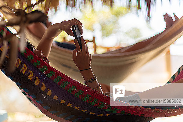 Woman checking a smart phone  lying in a hammock in the shade.