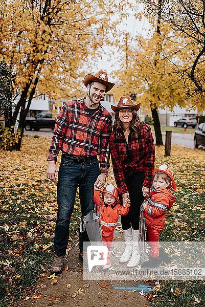 Eine Familie mit zwei Kindern  die für Halloween als Feuerwehrmänner verkleidet sind  posieren für ein Foto in einem mit Blättern übersäten Park.