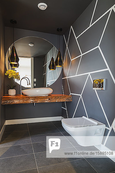 Interior view of modern bathroom with dark grey floor tiles and walls with geometric pattern  round wall mirror over basin on wooden railway sleeper and wall mounted toilet.