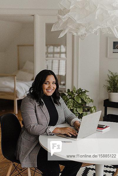 Frau mit langem  dunklem Haar sitzt am Esstisch und schaut auf einen Laptop-Computer.