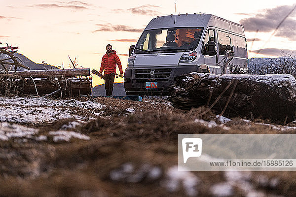 Man by a camper van carrying skis in a rocky wintry landscape.