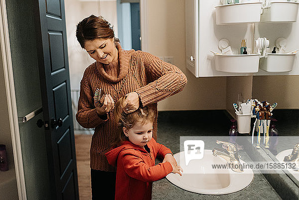 A woman brushing her daughters hair while standing in the bathroom.