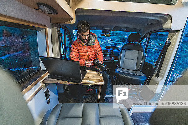 A man sitting in his campervan at a table with a laptop open looking at a camera.