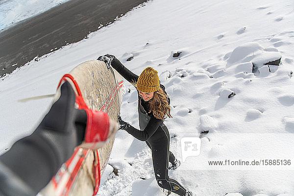 Eine Frau mit Neoprenanzug und Wollmütze hebt ein Surfbrett hoch  während sie an einem verschneiten Strand steht.