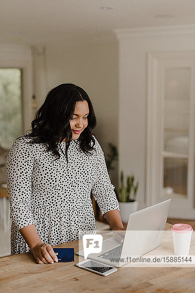 Woman with long dark hair standing at kitchen counter  looking at laptop computer.