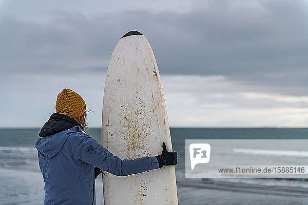 Rear view of a woman holding a surfboard standing on a snowy beach and looking out to sea.