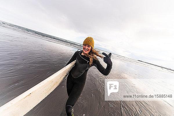 Eine Frau  die einen Neoprenanzug trägt und mit einem Surfbrett über einen schwarzen Strand mit dem Meer im Hintergrund läuft.