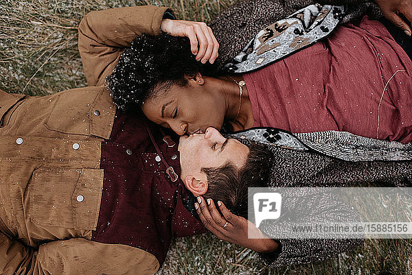 Draufsicht auf eine schwarze Frau und einen weißen Mann am Boden  die sich küssen.