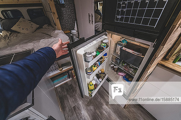 A hand opening the campervan fridge door which is filled with food and jars.