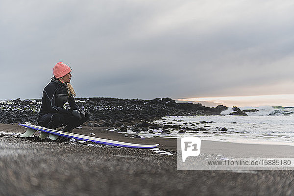 A woman sitting on her surfboard on a beach looking out to sea.