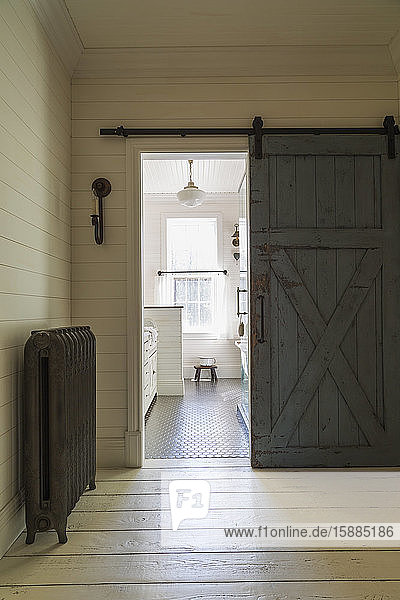 Blick durch eine Schiebetür auf ein Badezimmer mit schwarz gefliestem Boden  creme getäfelten Wänden und Schiebefenstern.