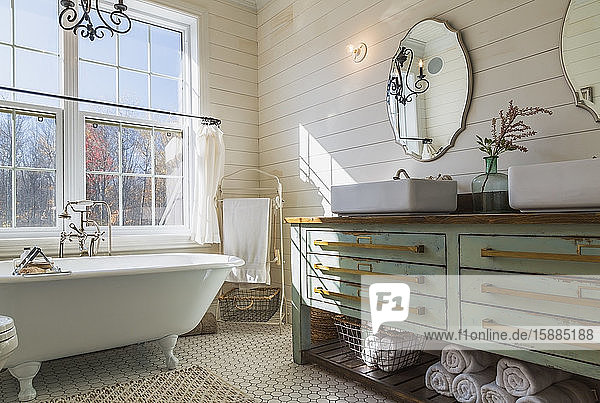 Bathroom with white roll top bath  cream tiled floor and wood panelled walls  green vanity unit with double hand basin.