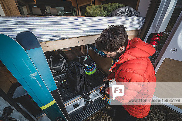 Man standing at the back of a van putting on ski boots standing next to a pair of skiis.