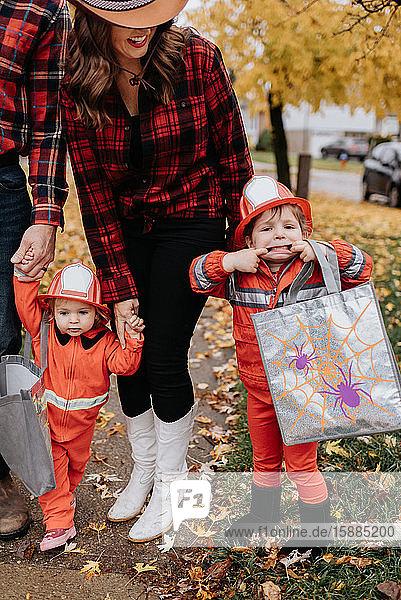 Eine Familie mit zwei Kindern  die für Halloween als Feuerwehrmänner verkleidet sind  spaziert durch einen mit Blättern übersäten Park.