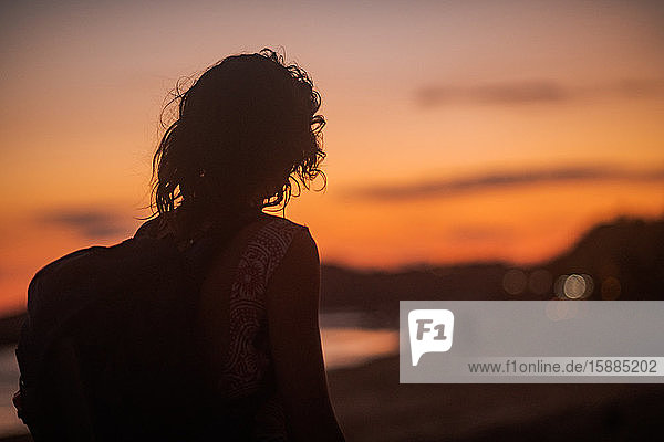 Silhouette of a young person with a backpack on a beach at sunset.