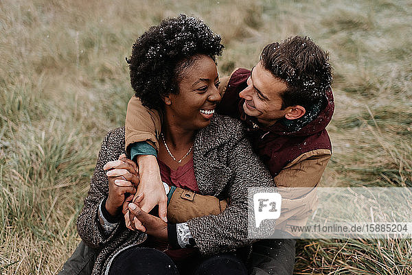 A black woman and white man hugging each other and smiling  sitting in a field of grass.