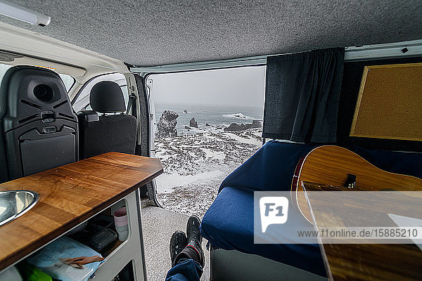 View through the door of a campervan towards a snowy beach and the sea. Winter road trip.