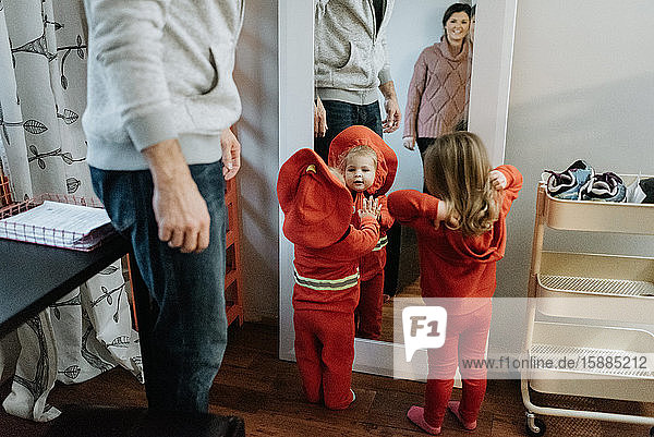 Two children looking at themselves in the mirror with their Halloween costumes while their mother and father look on.