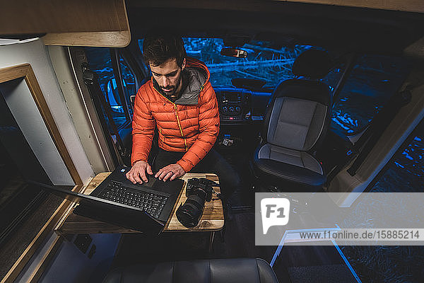A man sitting at a wooden table in his campervan working on his laptop.