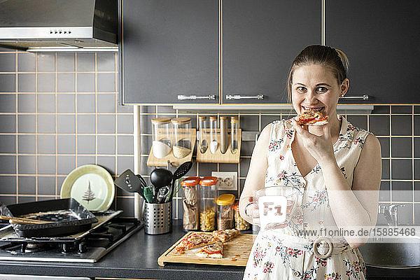Porträt einer glücklichen Frau  die in der Küche hausgemachte Pizza isst