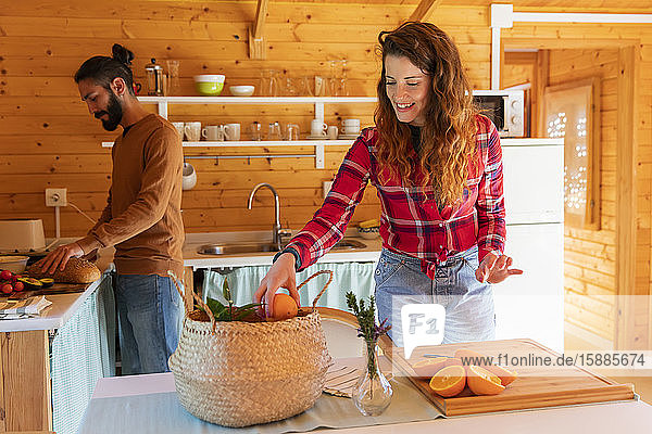 Frau mit Freund in einer Holzhütte bei der Zubereitung von Orangen