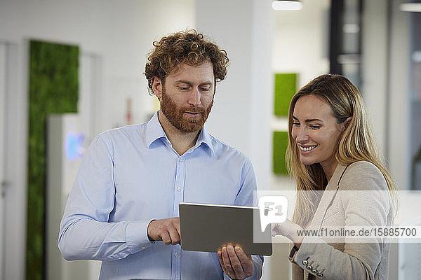 Geschäftsmann und Geschäftsfrau arbeiten zusammen mit Tablet im Büro