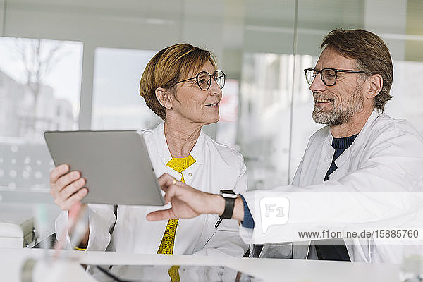 Zwei am Schreibtisch sitzende Ärzte mit Tablette