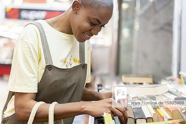 Lächelnde Frau sucht Bücher in einer Markthalle Lächelnde Frau sucht Bücher in einer Markthalle