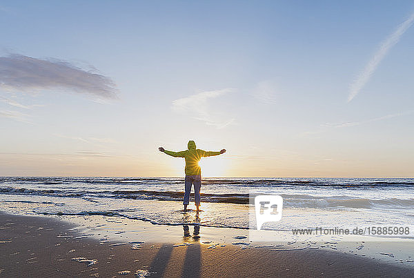Full length rear view of senior man with arms outstretched standing on shore while looking at sea against sky during sunset  North Sea Coast  Flanders  Belgium
