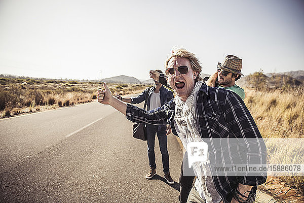 Three men hitchhiking at a country road