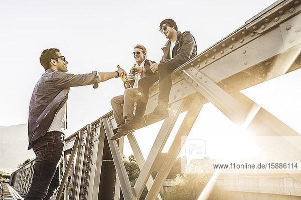 Drei Männer trinken Bier auf einer alten Eisenbahnbrücke
