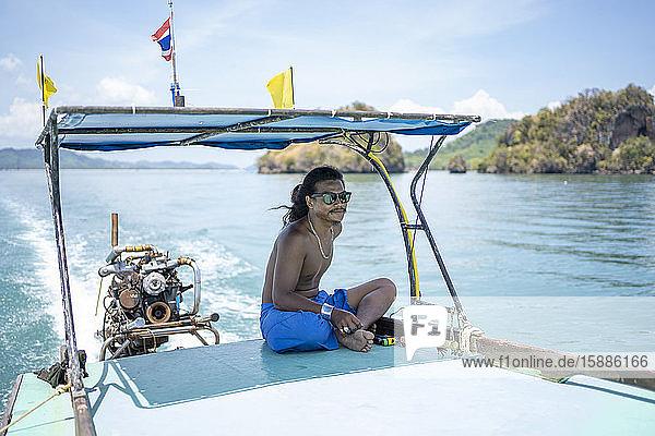 Junger einheimischer Mann auf einer Bootsfahrt  Ko Yao Yai  Thailand Junger einheimischer Mann auf einer Bootsfahrt, Ko Yao Yai, Thailand