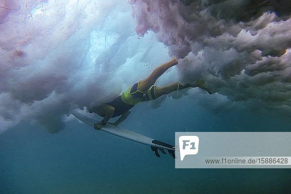 Indonesien  Unterwasseransicht eines erwachsenen Mannes  der mit einem Surfbrett in der Hand taucht