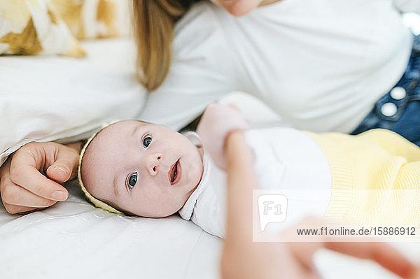 Porträt eines kleinen Mädchens  das auf dem Bett liegt und den Finger des Erwachsenen hält
