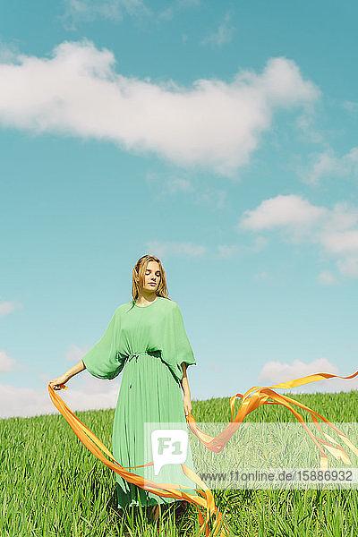 Junge Frau in grünem Kleid steht in einem Feld mit wehenden Bändern