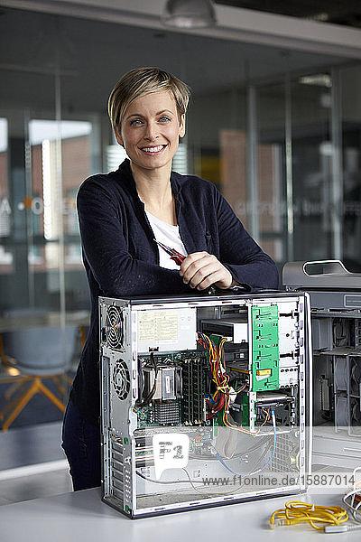 Porträt einer lächelnden Frau beim Zusammenbau eines Desktop-PCs im Büro