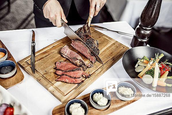 Hände des Kochs beim Schneiden von Tomahawk-Steak