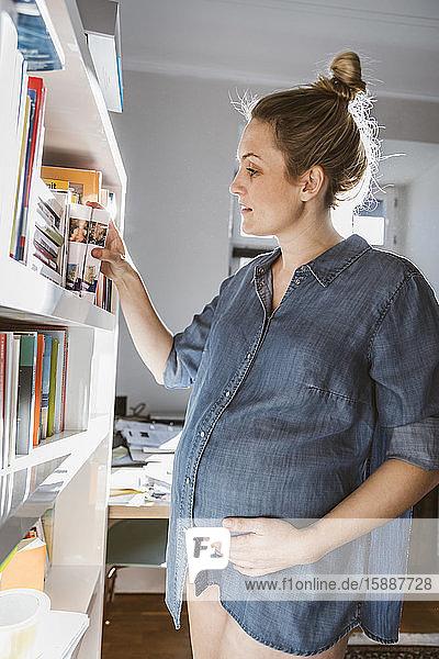 Schwangere Frau steht zu Hause am Bücherregal