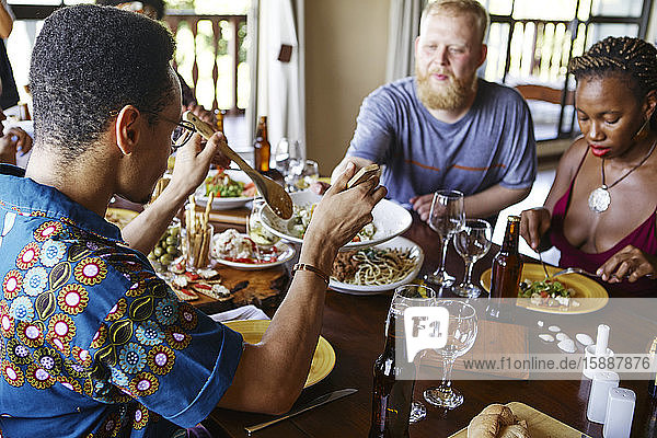 Multi-ethnic friends eating lunch while sitting at dining table