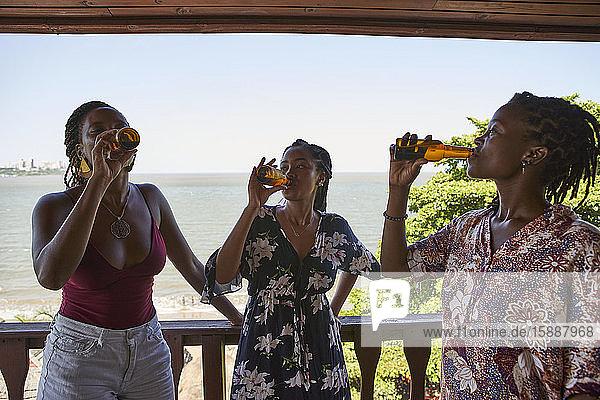 Junge Freundinnen trinken Bier  während sie auf dem Balkon gegen das Meer stehen