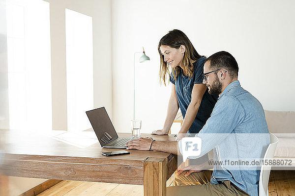 Lächelndes Paar bei der Arbeit am Laptop von zu Hause im Home-Office im modernen Wohnzimmer