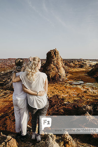 Rear view of female friends looking at volcanic landscape in Dallol Geothermal Area  Danakil Depression  Ethiopia  Afar
