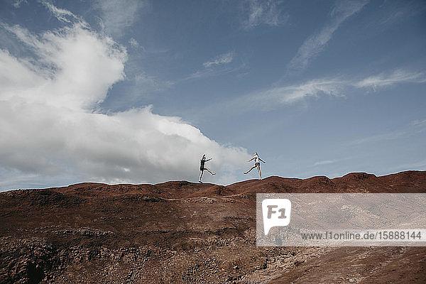 Fernblick von Freunden  die Yoga praktizieren  auf die dramatische Landschaft am Waimea Canyon  Kauai  Hawaii  USA
